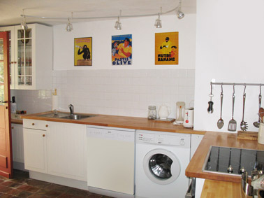 Kitchen with white units and solid beech work surfaces, halogen hob. There nostalgic tin advertising plaques on the wall featuring Banan, Pastis and Choky.