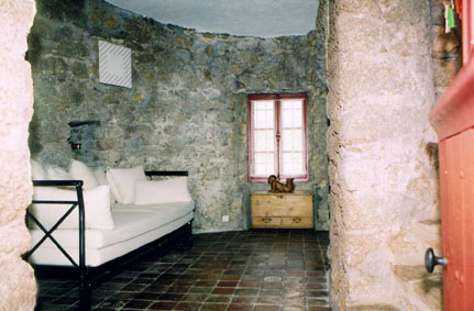 Ground floor of Moulin Tower viewed through the doorway. There is a wrought iron sofa bed with white mattress and cushions. The floor is tiled and the walls are natural stone. There is a small window opposite the door.