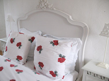 Close up shot of the bed showing the intricate carving on the white bed head. The bed linen is white with lovely photo realistic red roses.